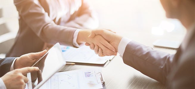 business people shaking hands over desk