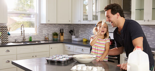 father and daughter in the kitchen having fun and baking