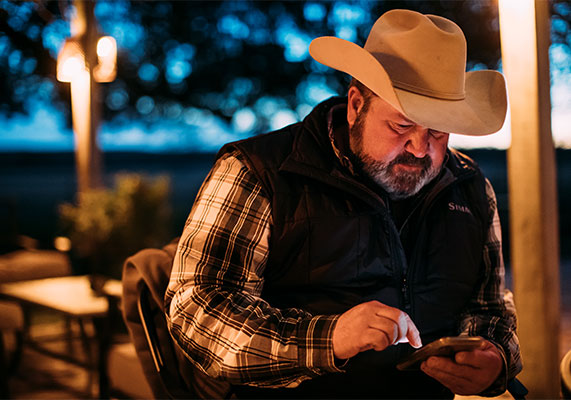 cowboy looking at his phone at dusk