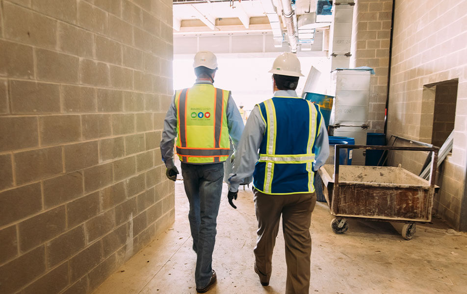 two construction workers walking through site